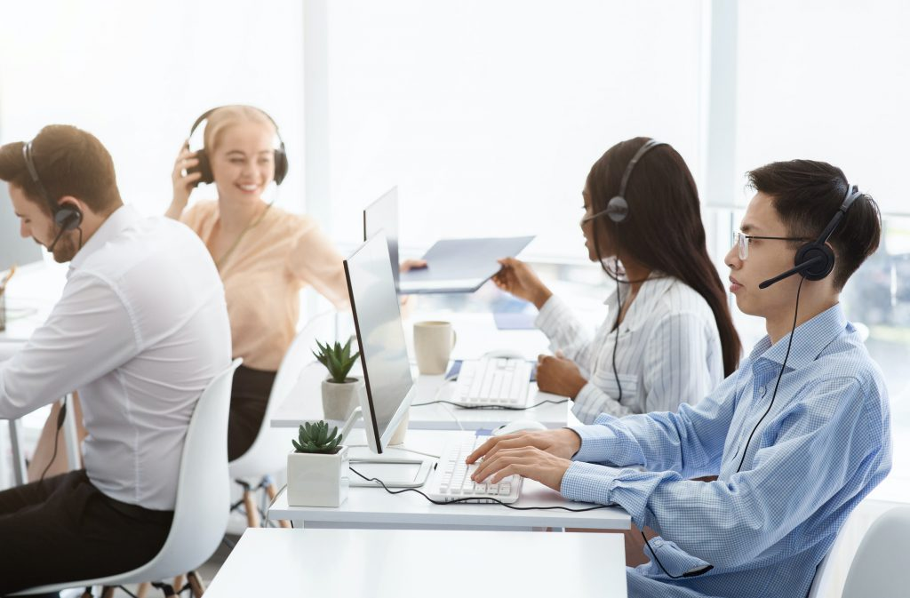 Team of technical support agents working on hotline at call center